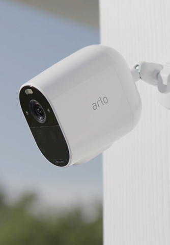 Arlo floodlight camera on a wall of a house.