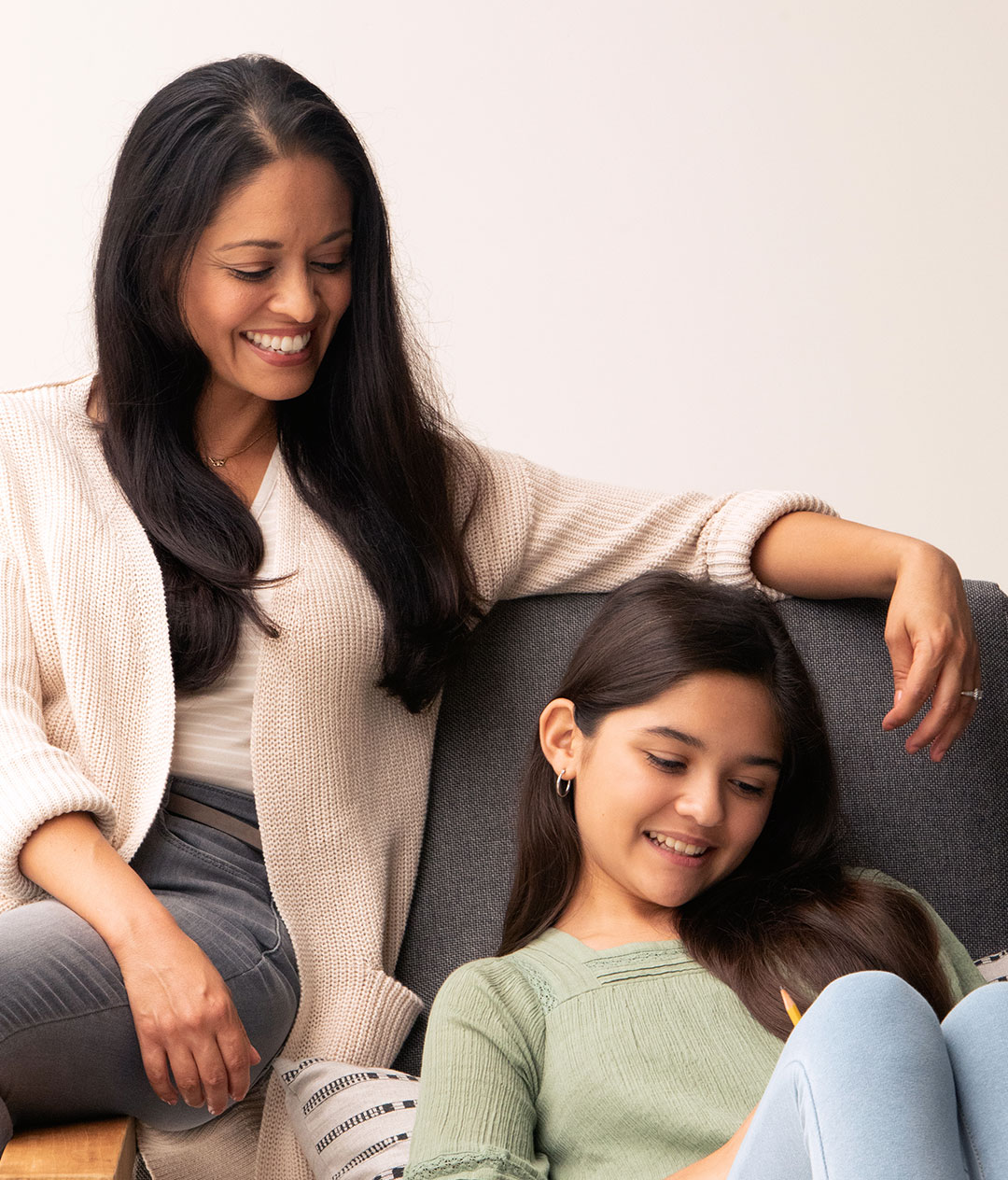 Image of mother and daughter at home sitting on couch