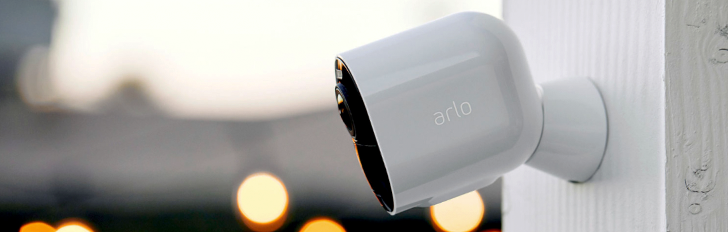 Arlo Ultra 2 Security Camera, mounted outside on white pillar, with bokeh lights in background