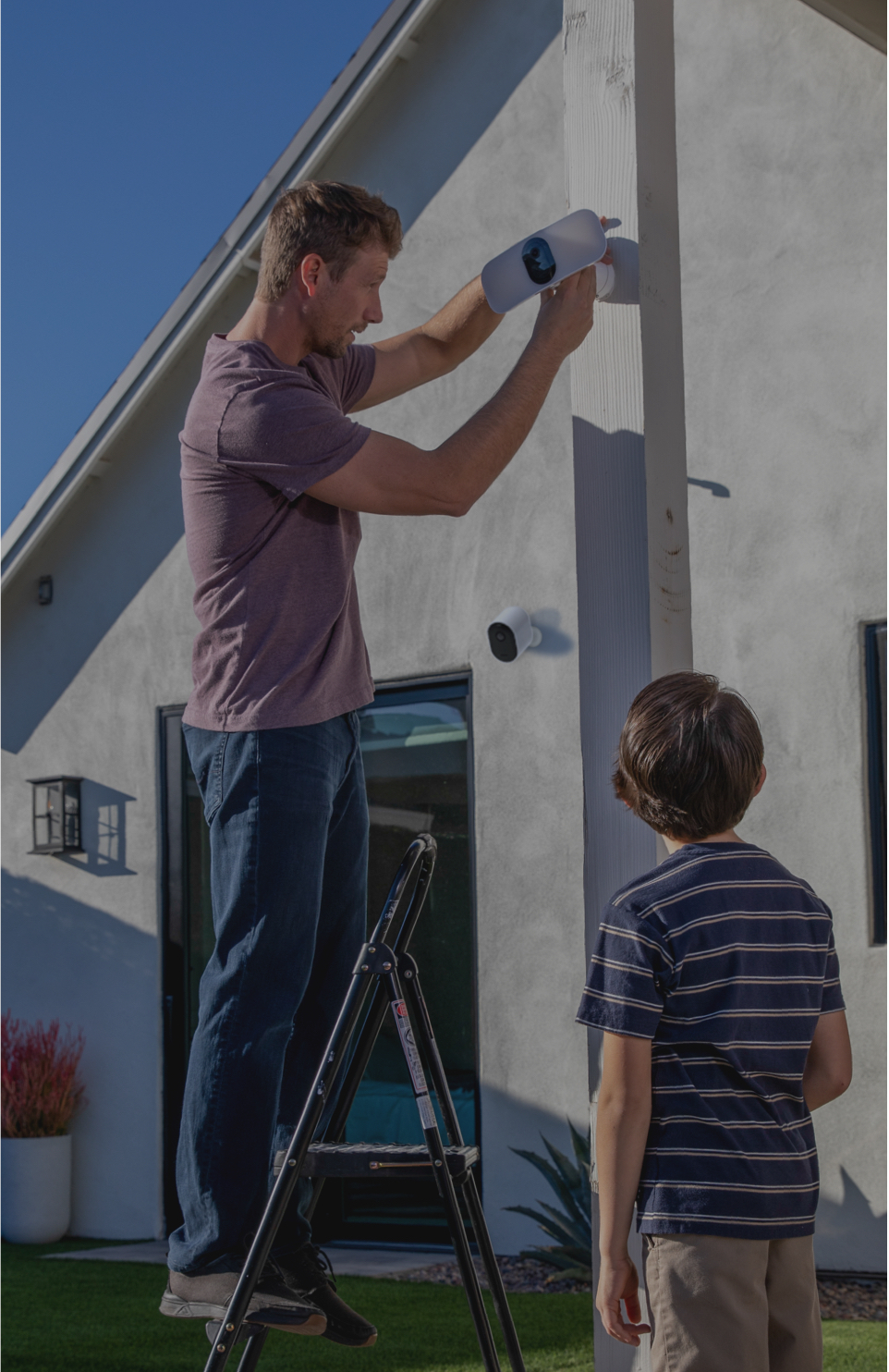Father and son in backyard with Arlo Pro 3 Floodlight