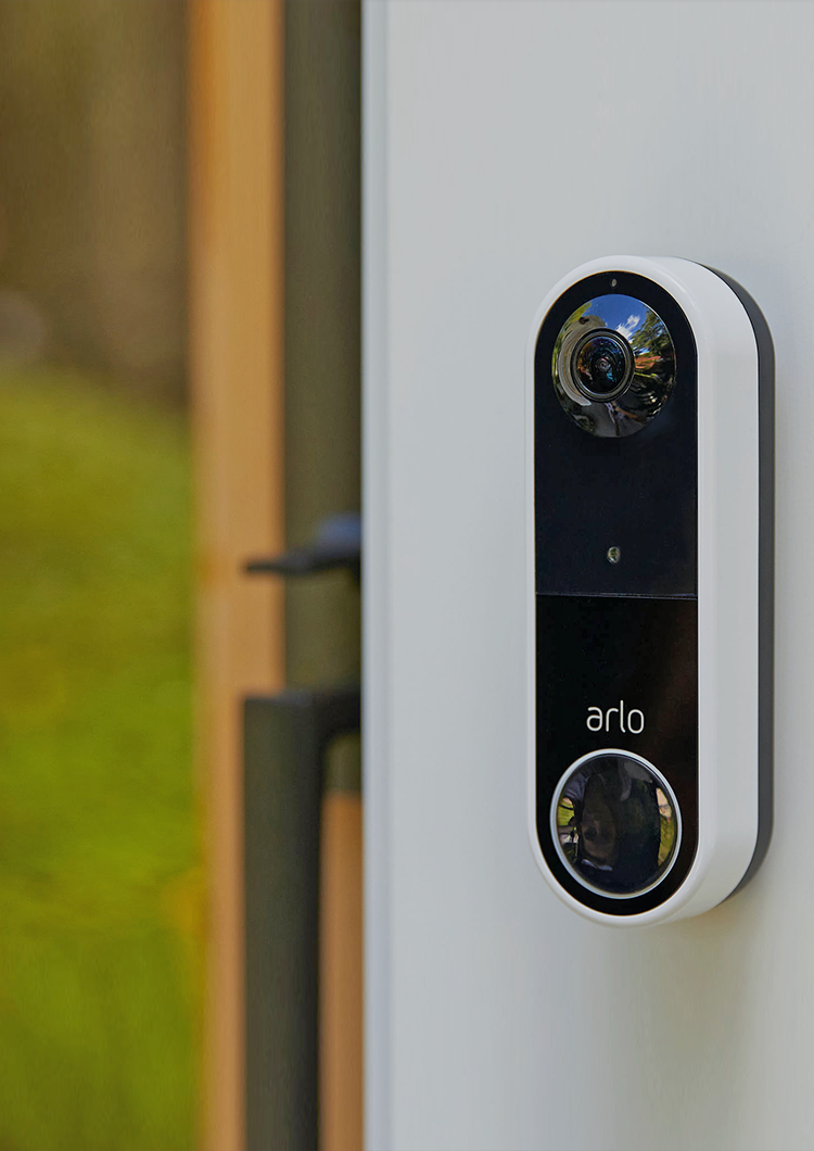 Man standing outside with a dog with Arlo Pro 4 and Video Doorbell on the front porch of home